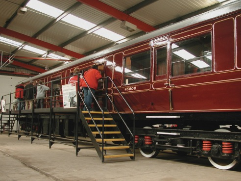 Visitors looking at a railway carriage in the West Shed museum