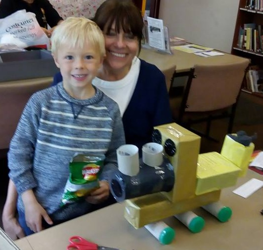 A Mum and her child making a model train from recycling material.