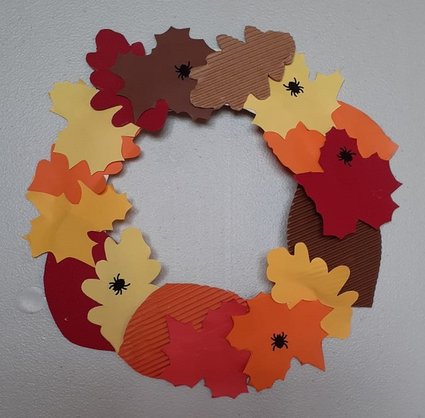 A decorative wreath made out of paper shapes of leaves.