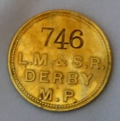 Round metal pay check with a worker's identity number stamped on.