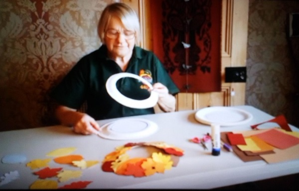 Demonstrating cutting the middle out of a paper plate.