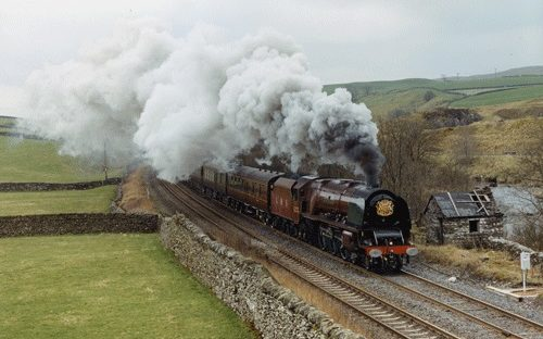 Steam locomotive Duchess of Sutherland travelling through the countryside.