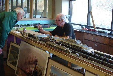 Two volunteers working on a model railway.