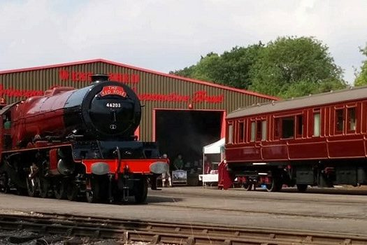 A steam locomotive and railway carriage outside the West Shed.