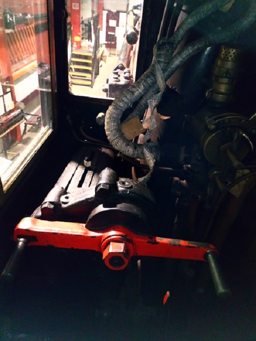 A steam locomotive reversing mechanism in the driver's cab.